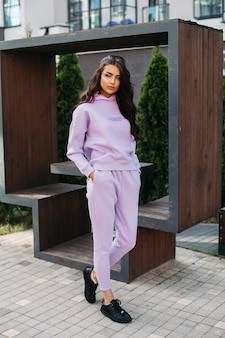 Bild einer hübschen kaukasischen frau in lila sportanzug und schwarzen turnschuhen hält ihre hände in den taschen