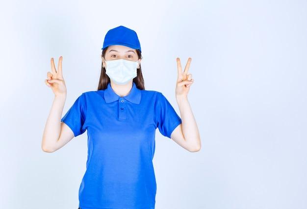 Bild einer jungen frau in uniform, die eine medizinische maske trägt und ein siegeszeichen zeigt.