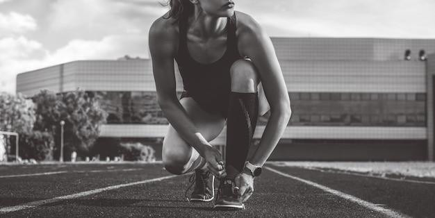 Bild einer jungen läuferin, die ihre schuhe auf einer stadionbahn schnürt. sportkonzept.