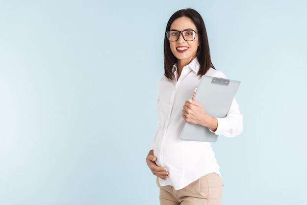 Bild einer jungen schwangeren geschäftsfrau lokalisiert, die zwischenablage hält.