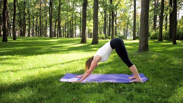 Bild einer lächelnden glücklichen frau mittleren alters, die meditiert und yoga-übungen auf gras im wald macht. frau, die sich um ihre körperliche und geistige gesundheit kümmert, während sie fitness und stretching im park übt
