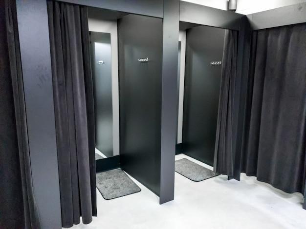 Bild einer leeren umkleidekabine im einkaufszentrum mit dunkelschwarzen vorhängen und spiegeln