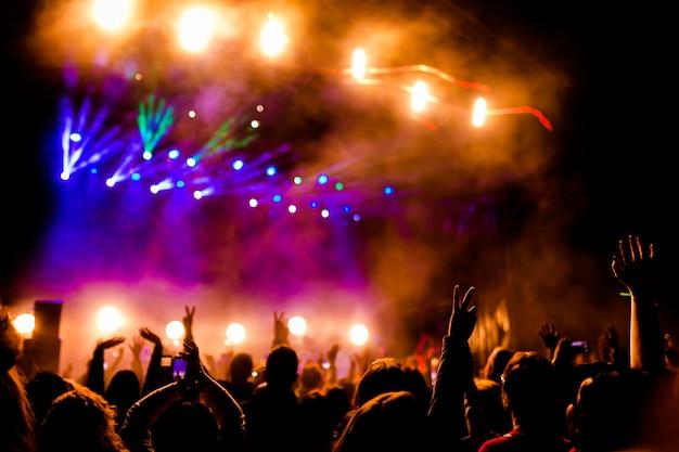 Bild einer menge leute, die nachtaufführung genießen, große unerkennbare menge, die mit erhobenen händen und handys auf konzert tanzt. nachtleben