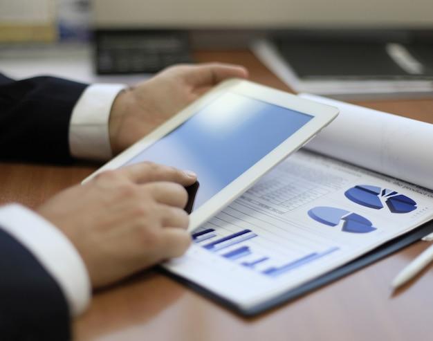 Bild einer menschlichen hand, die in der arbeitsumgebung bei einem meeting auf den touchscreen zeigt