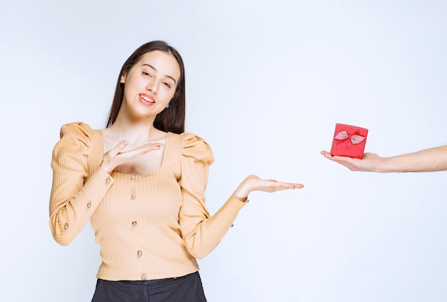 Bild einer netten jungen frau, die auf eine rote kleine geschenkbox steht und zeigt.