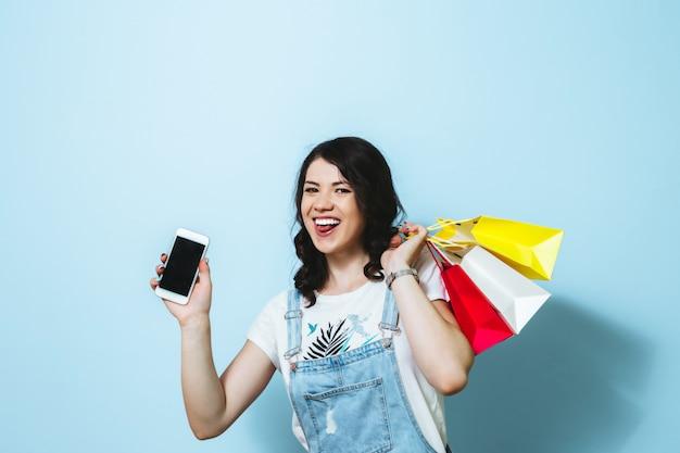 Bild einer netten jungen frau, die handy des leeren bildschirms beim tragen lokalisiert über gelben wandeinkaufstaschen zeigt