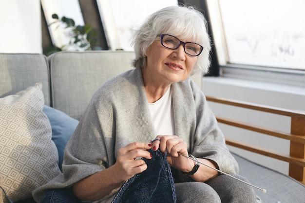 Bild einer ordentlichen frau im ruhestand, die einen breiten schal und eine brille trägt und einen warmen pullover für ihre tochter strickt. attraktive ältere strickerin, die von zu hause aus arbeitet und handgefertigte winterkleidung zum verkauf anbietet
