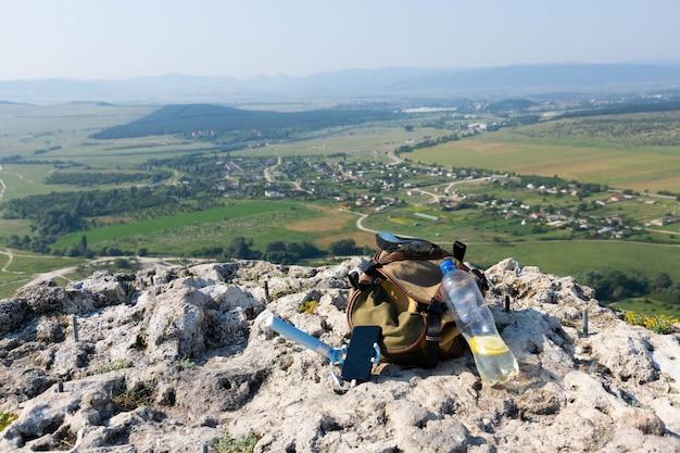 Bild einer plastikflasche und eines touristenrucksacks auf einer bergklippe in freier wildbahn. foto in hoher qualität