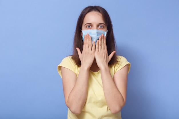 Bild einer schockierten, beeindruckten jungen frau, die direkt in die kamera schaut, die augen weit öffnet, die hände in den mund nimmt, sich in einer antibakteriellen maske befindet und angst vor einer coronavirus-infektion hat. covid19-konzept.