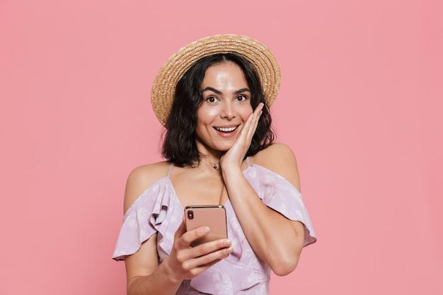 Bild einer schockierten, schönen jungen, glücklichen frau, die isoliert über rosafarbener wand mit handy posiert.