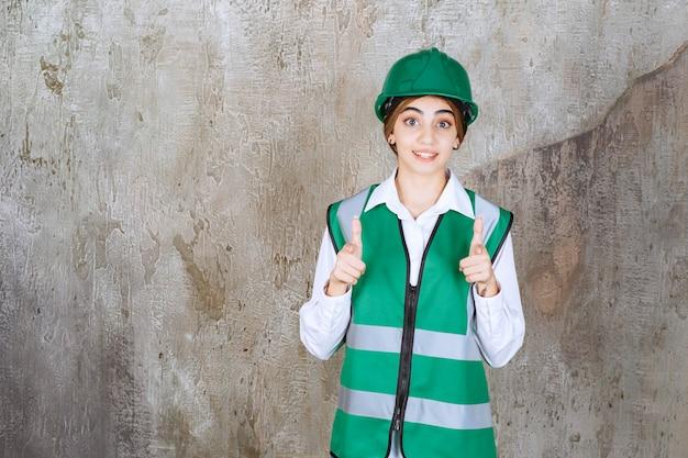 Bild einer schönen architektin im grünen helm, die auf etwas zeigt