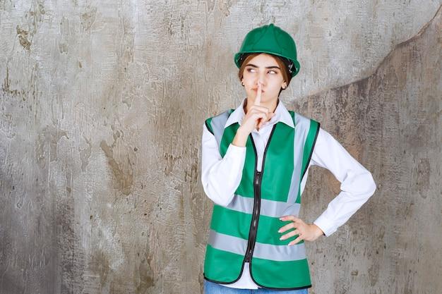 Bild einer schönen architektin im grünen helm, die über marmor steht