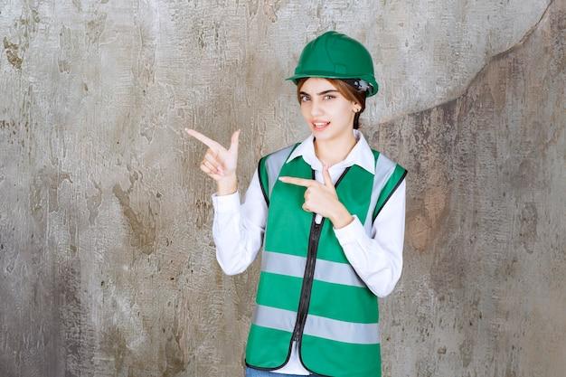 Bild einer schönen architektin mit grünem helm, die auf etwas zeigt