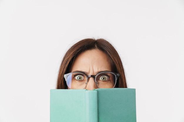 Bild einer schönen brünetten erwachsenen frau mit brille, die die stirn runzelt und ihr gesicht mit buch isoliert auf weiß