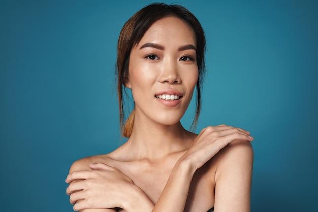 Bild einer schönen erfreuten positiven lächelnden asiatischen frau, die nackt auf blauer wand lokalisiert aufwirft.