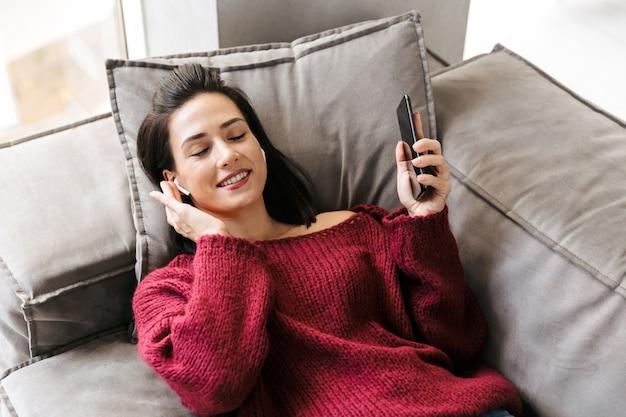 Bild einer schönen frau drinnen im haus auf sofa, das musik mit kopfhörern hört.