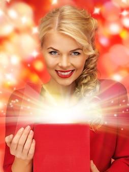 Bild einer schönen frau im roten kleid mit geöffneter geschenkbox