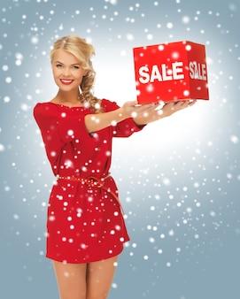 Bild einer schönen frau im roten kleid mit verkaufsschild