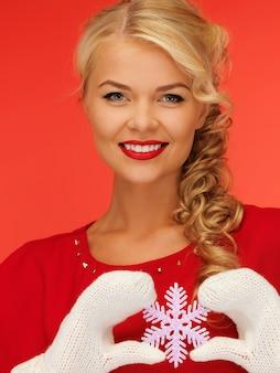 Bild einer schönen frau in handschuhen und rotem kleid mit schneeflocke