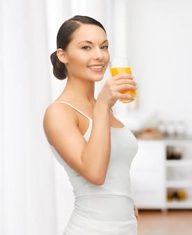 Bild einer schönen frau mit einem glas saft in der küche