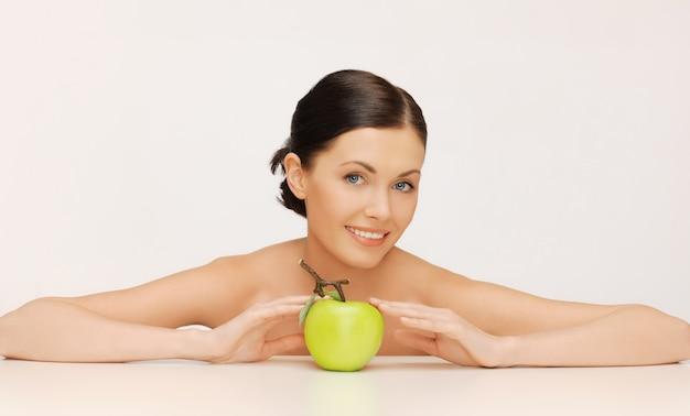 Bild einer schönen frau mit grünem apfel