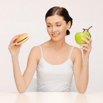 Bild einer schönen frau mit hamburger und apfel
