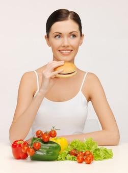 Bild einer schönen frau mit hamburger und gemüse