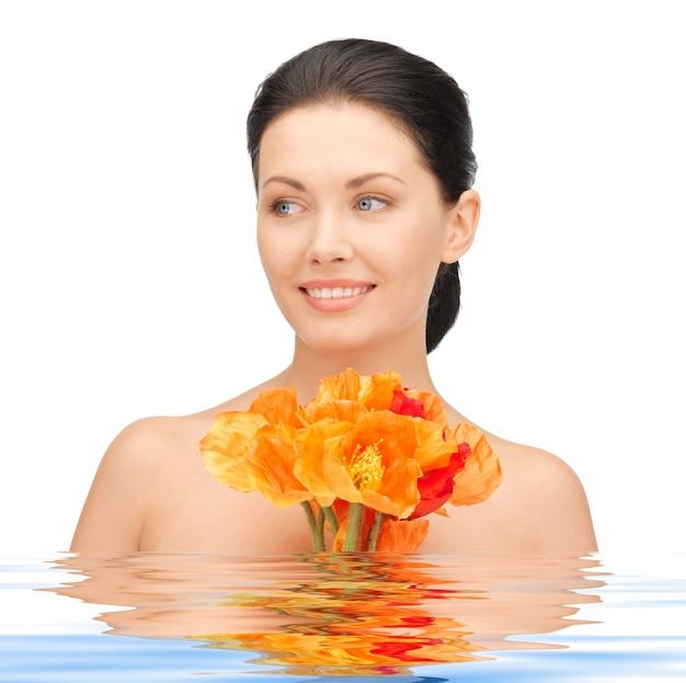 Bild einer schönen frau mit roten blumen im wasser