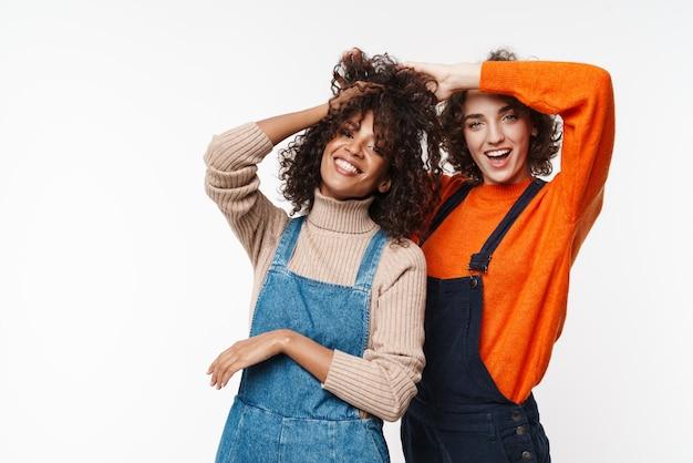 Bild einer schönen fröhlichen fröhlichen optimistischen zwei gemischtrassigen freundinnen in denim-overalls