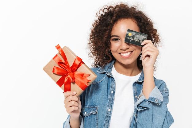 Bild einer schönen glücklichen jungen afrikanischen frau, die lokalisiert über der weißen wand aufwirft, die gegenwärtige geschenkbox und kreditkarte hält.