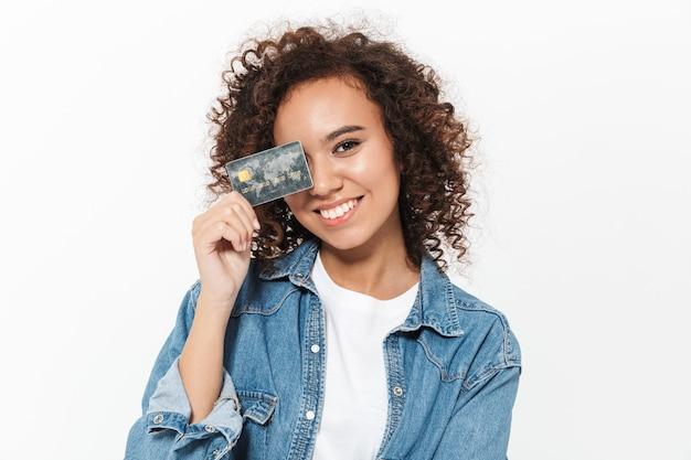Bild einer schönen glücklichen jungen afrikanischen frau, die lokalisiert über der weißen wand aufwirft, die kreditkarte hält.