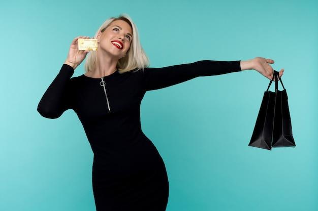 Bild einer schönen glücklichen jungen blonden frau, die lokal über blauem wandhintergrund hält, der einkaufstaschen hält