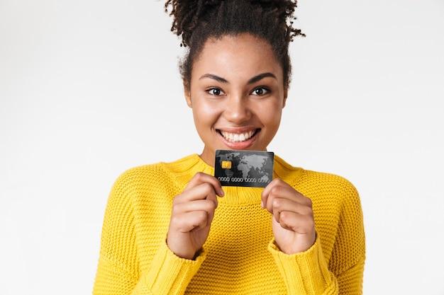 Bild einer schönen jungen afrikanischen aufgeregten emotionalen glücklichen frau, die über weiße wand hält, die kreditkarte hält.