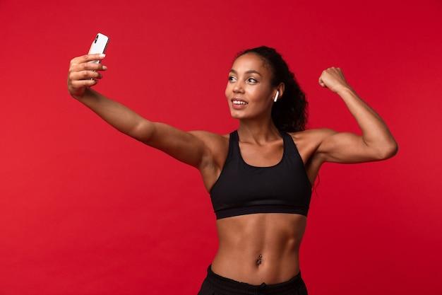 Bild einer schönen jungen afrikanischen sportfitnessfrau, die lokalisiert über der roten wandwand aufhört, die musik mit kopfhörern hört, nehmen ein selfie durch handy, das bizeps zeigt.