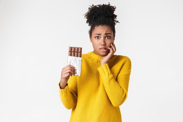 Bild einer schönen jungen afrikanischen verwirrten frau, die über weiße wand, die süßigkeiten schokolade hält aufwirft.