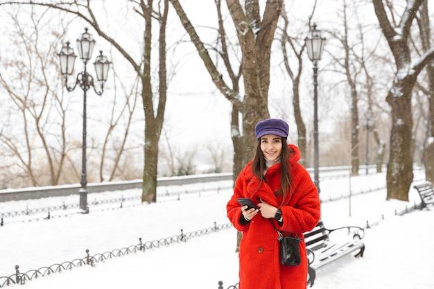 Bild einer schönen jungen frau, die handy im freien im schneewinter geht.