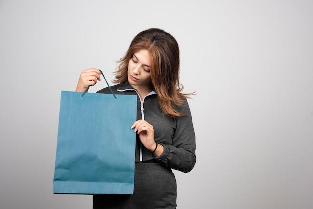 Bild einer schönen jungen frau, die ihre blaue einkaufstasche betrachtet.
