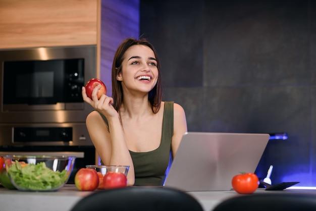 Bild einer schönen jungen frau mit apfel, der drinnen mit laptop-computer sitzt.