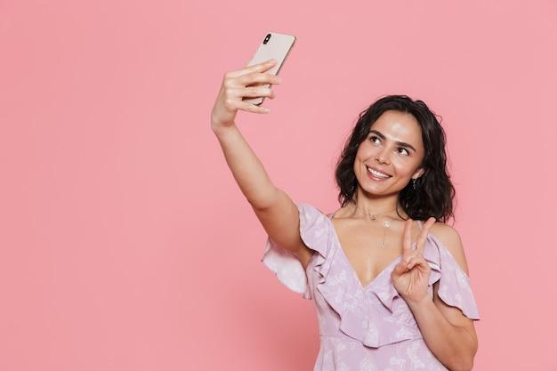 Bild einer schönen jungen glücklichen frau, die isoliert über rosa wand posiert, macht ein selfie per telefon.