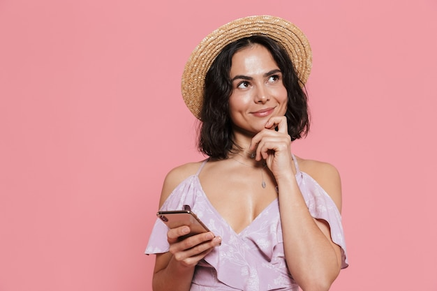 Bild einer schönen jungen glücklichen frau posiert isoliert über rosa wand mit handy.