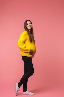 Bild einer schönen jungen schwangeren emotionalen frau, die lokal über rosa aufwirft.