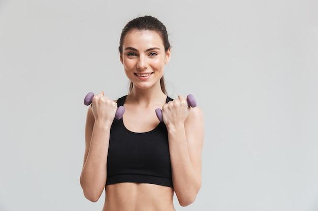 Bild einer schönen jungen sport-fitness-frau macht übungen mit hanteln isoliert über grauer wand.