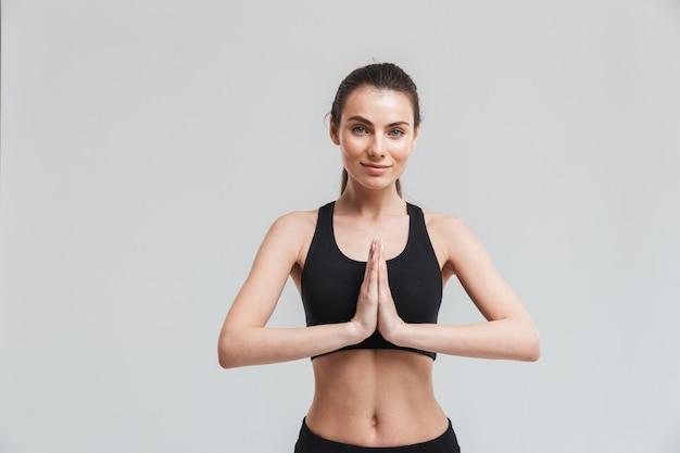 Bild einer schönen jungen sporteignungsfrau machen übungen, die über grauer wand lokalisiert werden, meditieren.
