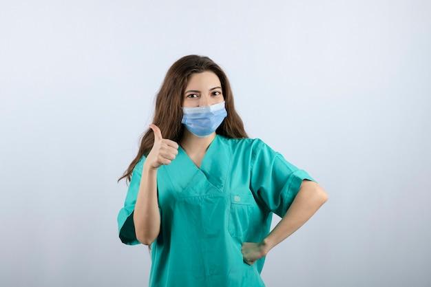 Bild einer schönen krankenschwester in grüner uniform, die einen daumen nach oben zeigt