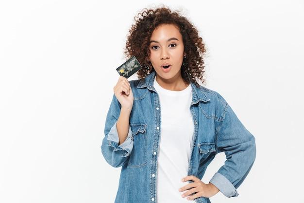 Bild einer schönen schockierten jungen afrikanischen frau, die isoliert über der weißen wand posiert, die kreditkarte hält.