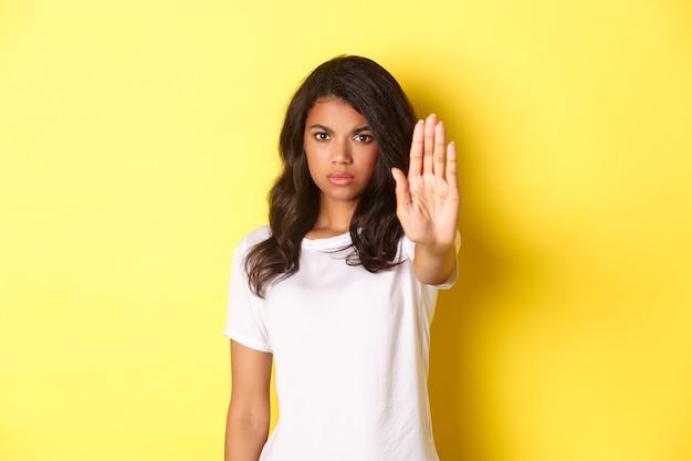 Bild einer selbstbewussten und ernsthaften afroamerikanischen frau, die nein sagt, ein stoppschild zeigt und unzufrieden die stirn runzelt, etwas schlimmes verbieten, vor gelbem hintergrund stehen.