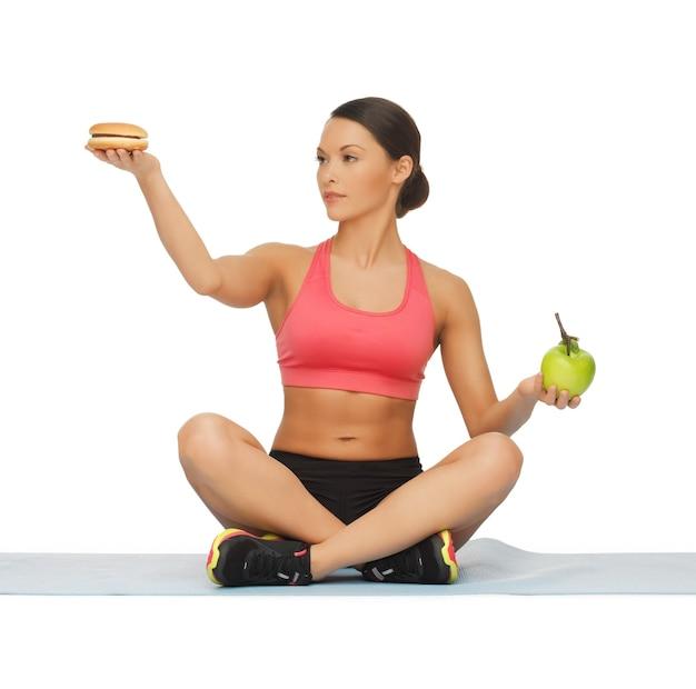 Bild einer sportlichen frau mit apfel und hamburger