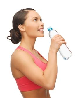 Bild einer sportlichen frau mit einer flasche wasser