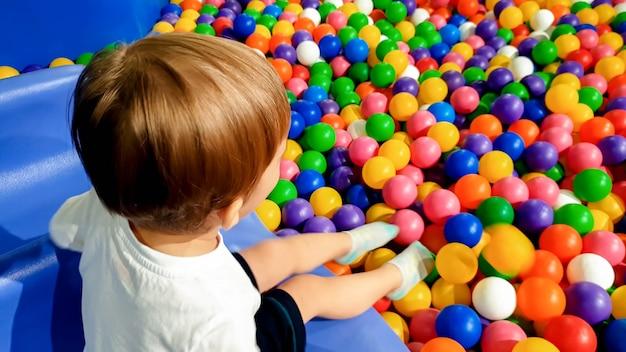 Bild eines 3 jahre alten kleinkindjungen, der auf dem spielplatz mit vielen kleinen bunten plastikkugeln spielt und spaß hat. kind, das vergnügungspark im einkaufszentrum genießt enjoying