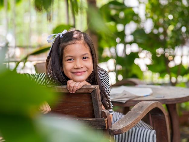 Bild eines 8-jährigen asiatischen mädchens, das in ihrem hinterhof liest oder hausaufgaben macht. schulkind im urlaub